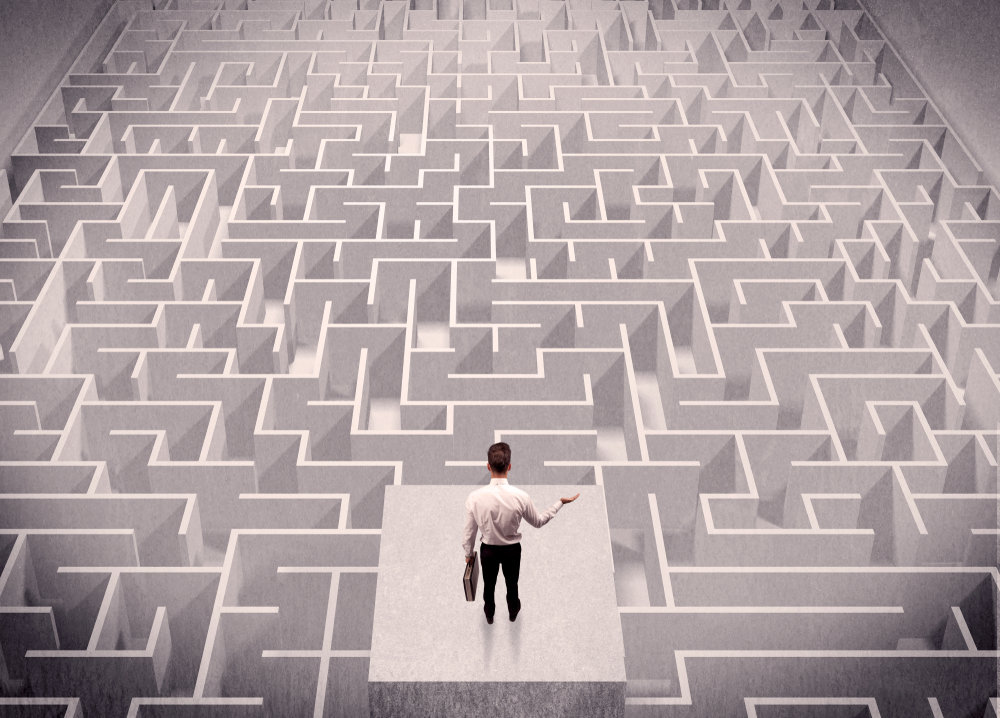 A confused businessman thinking while standing on a square platform above a detailed maze
