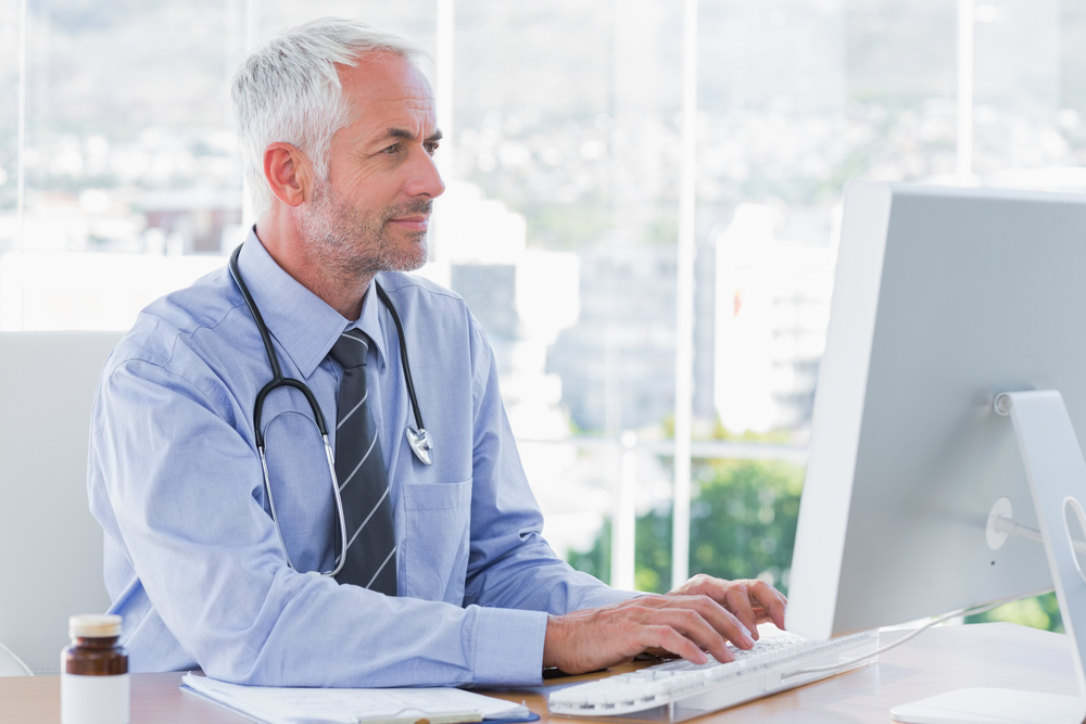 Doctor typing on his computer in the office-1