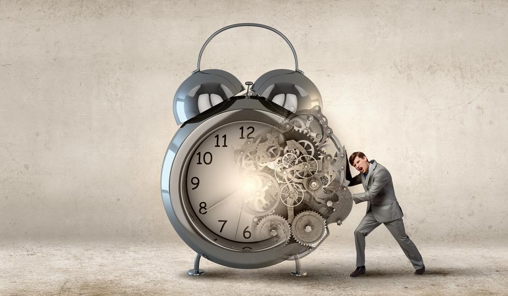 Businessman making effort to move alarm clock