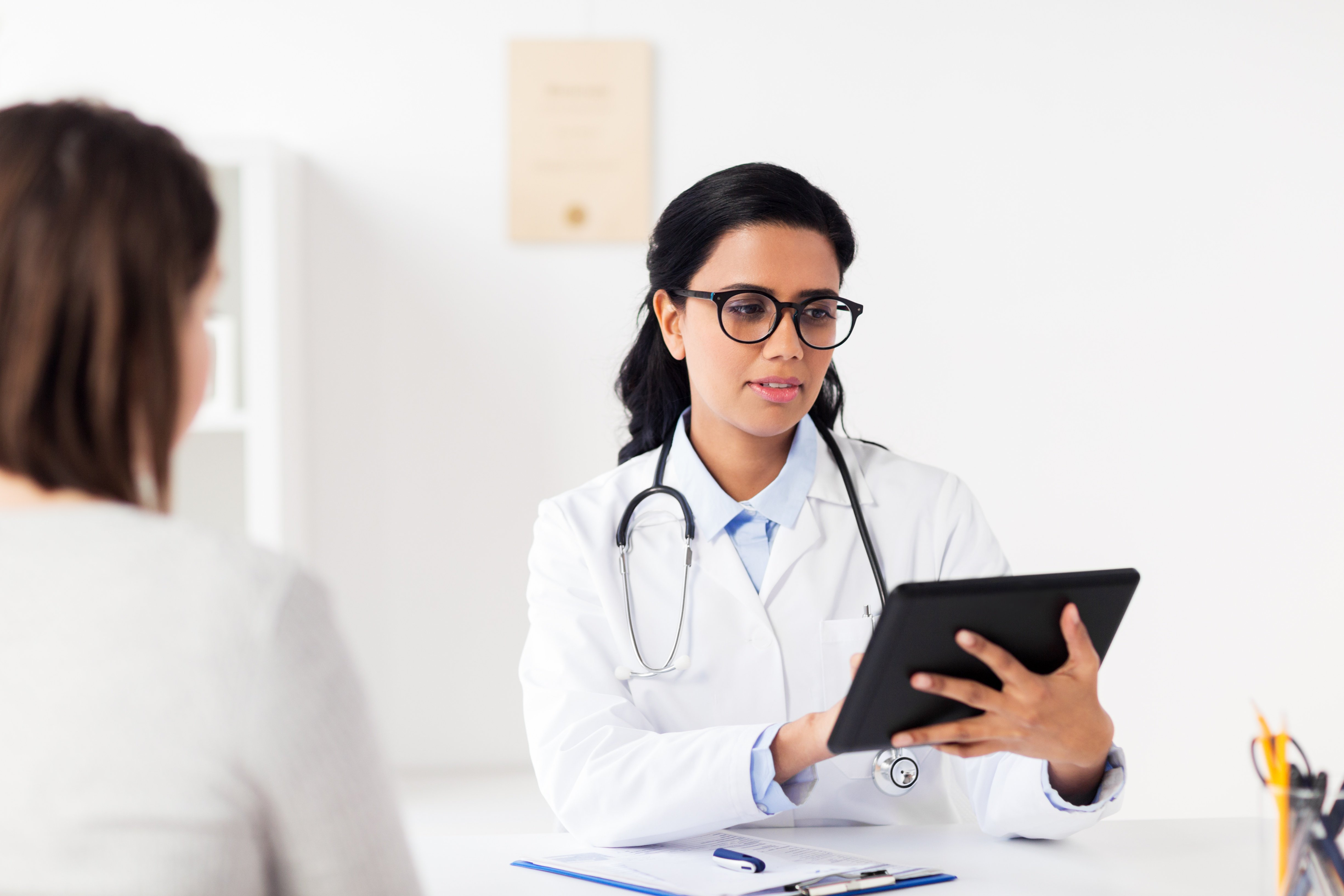 doctor-with-tablet-pc-and-woman-at-hospital-PA6CNHH