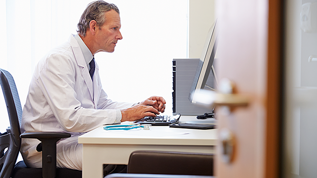 Doctor sitting at a computer using telemedicine